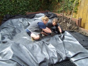 Michele and Ethan preparing a liner on a Pondless Waterfall